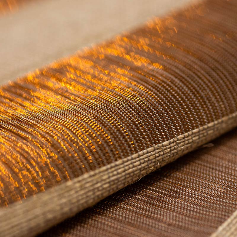 Closeup to Tenza weave textile handwoven in plantain fiber and copper threads.