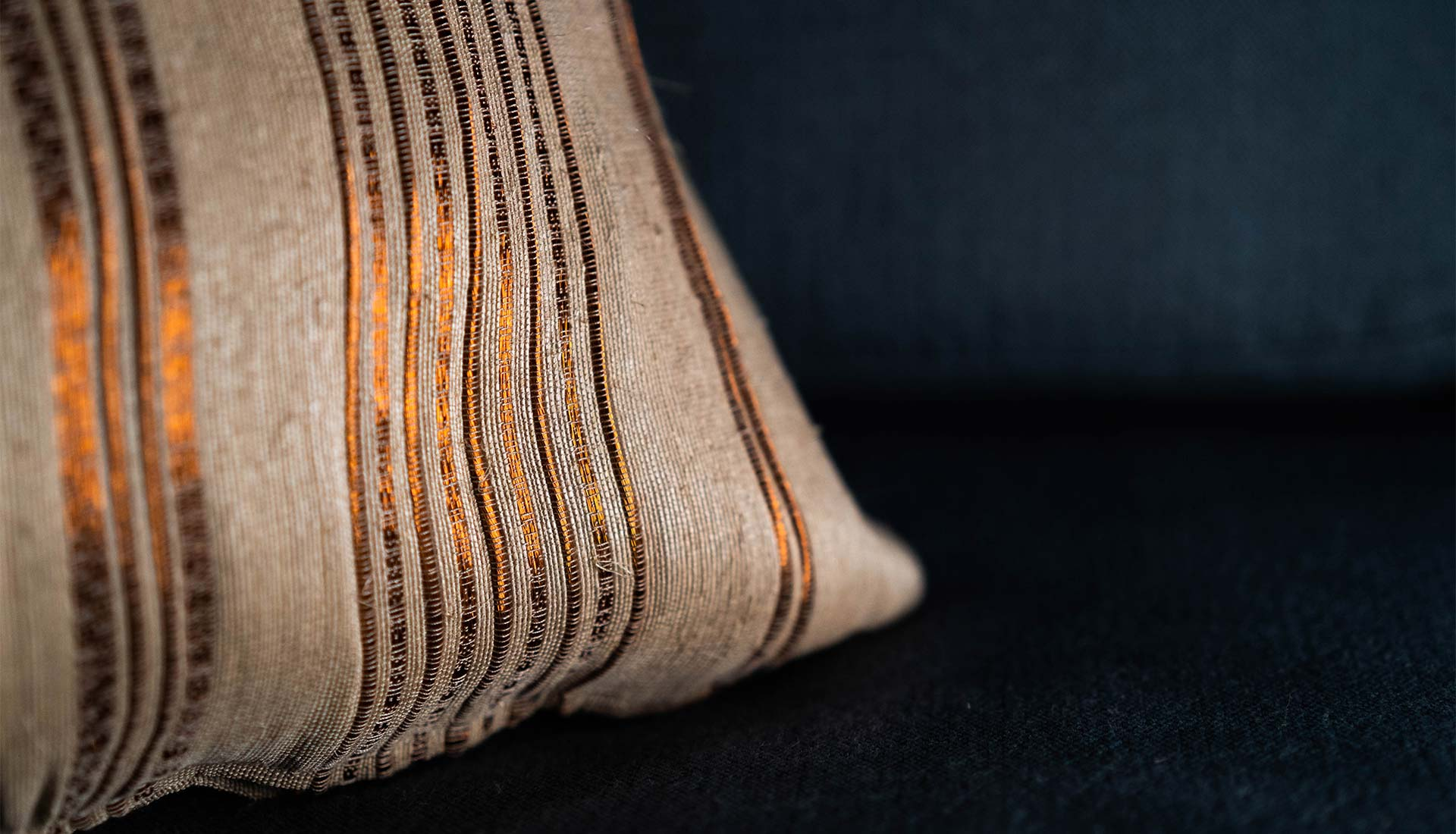 Closeup to plantain fiber and copper threads handwoven pillow
