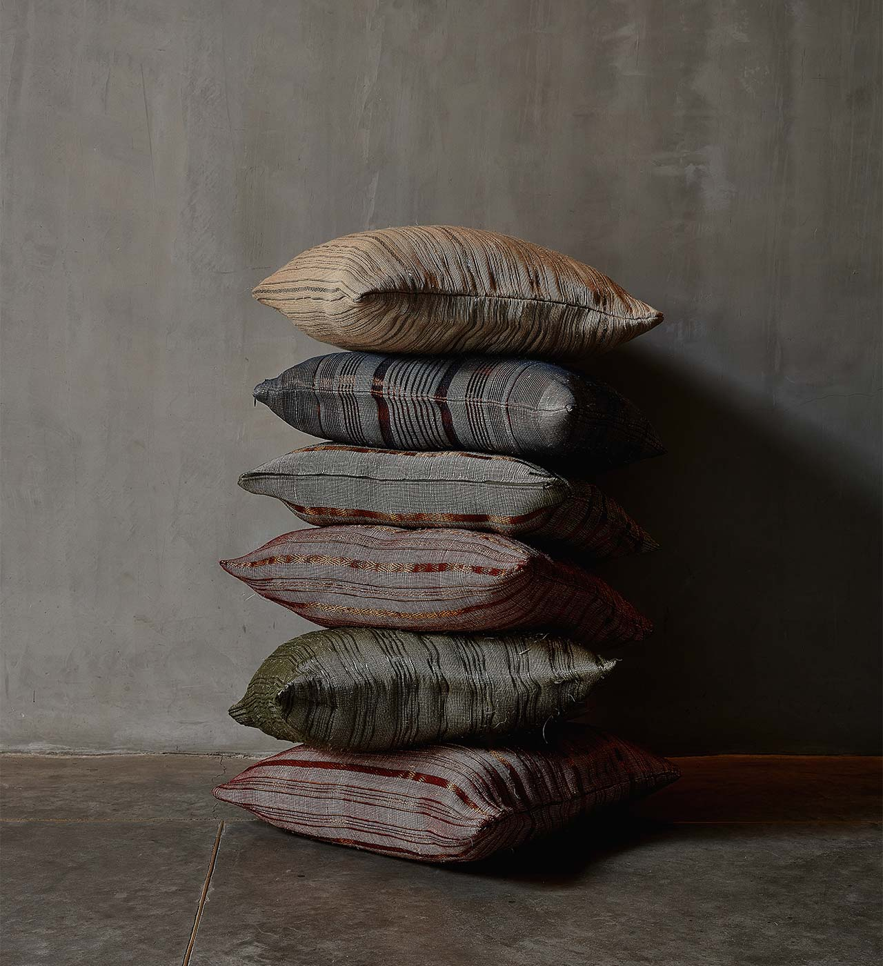 Stacked pillows with concrete background. Handwoven navy blue, olive green, natural, and burgundy pillows in plantain fiber and copper threads or stainless-steel threads.